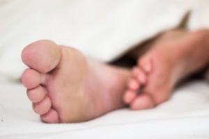 Foto van twee voeten die onder het laken vandaan steken. Schijnbaar in alle rust.