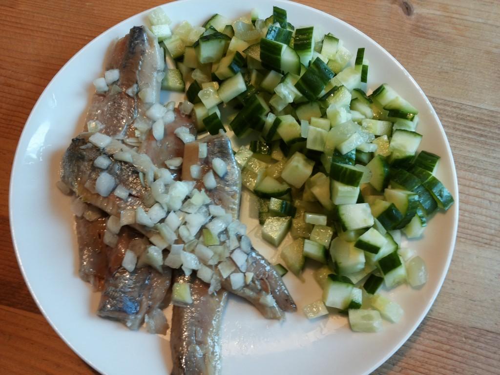 Zoute haring met uitjes naast komkommer met augurksalade