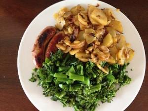 broccolistronk met roosjes gekookt naast aardappels en een worstje