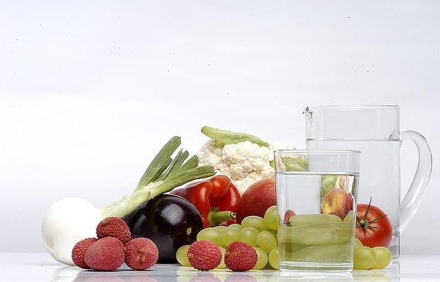 Eet je calorieën en drink je water verbeeld in een karaf water en vers fruit en groente ernaast.